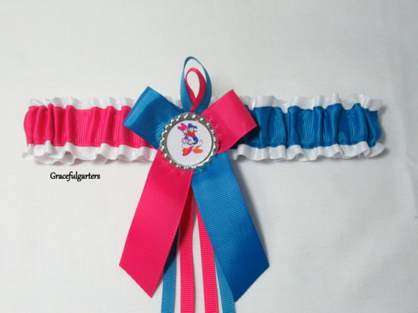 Cerise pink and Turquoise Blue grosgrain with white grosgrain backing ribbon. Matching grosgrain bow and ribbon loops with silver crown/glass top with Donald and Daffy Duck inside
