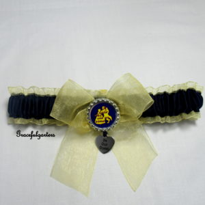 Gold organza trimmed garter with navy blue satin and gold organza bow. Silver crown/glass top in the centre with a tale as old as time and hanging from crown is silver heart with be our guest printed on it.